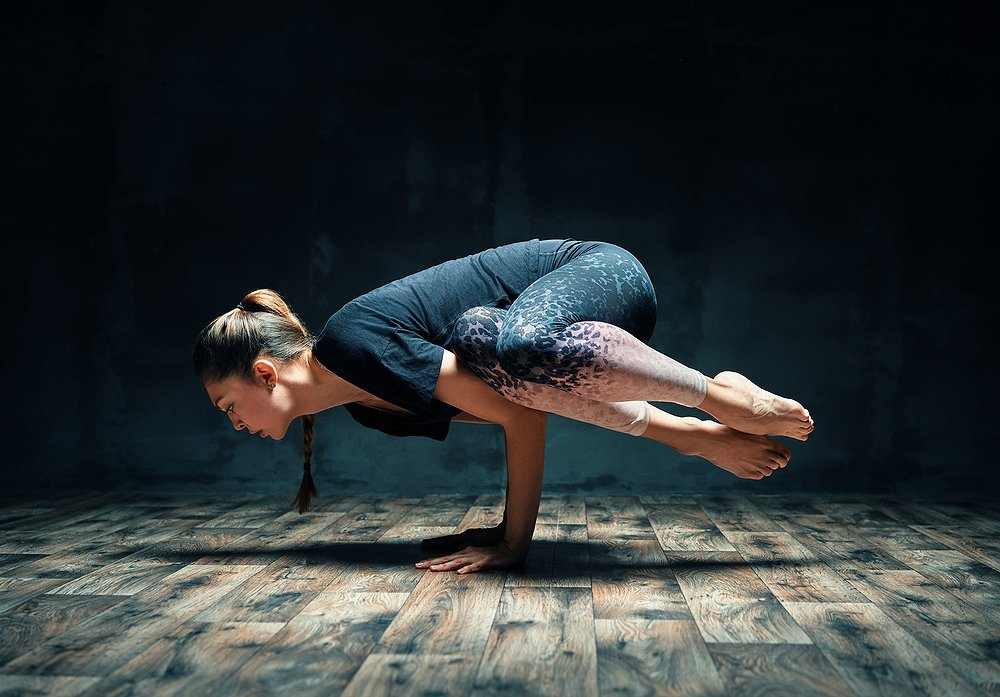 Young woman practicing yoga doing side crane pose in
