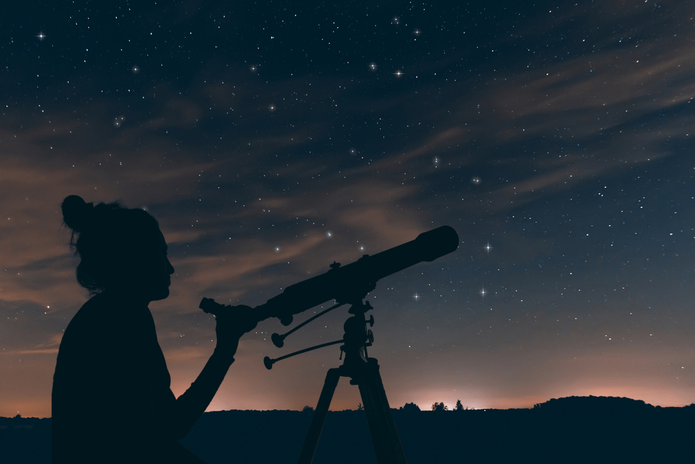 Woman with astronomical telescope. Night sky, with clouds and co